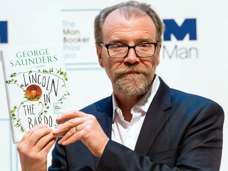 """George Saunders holds up a trophy after winning the Folio Prize at the St Pancras Renaissance Hotel in London, Monday, March 10, 2014. The American writer has won the 40,000 pound ($67,000) Folio Prize for literature with his humorous and disturbing short-story collection """"Tenth of December."""" The chair of the judging panel, poet Lavinia Greenlaw, said Monday that Saunders' """"darkly playful"""" stories explore """"the human self under ordinary and extraordinary pressure."""" Saunders beat seven other finalists, including Kent Haruf, Rachel Kushner, Anne Carson and Eimear McBride. (Xinhua/Ray Tang) UNITED KINGDOM OUT NO SALES NO ARCHIVE ORG XMIT: LON813"""