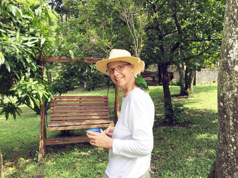 Fernanda Falbo Bandeira de Mello (1959-2017) em seu terreno de Extrema, acompanhada de seu Lóris Arco-Íris de estimação, Billy