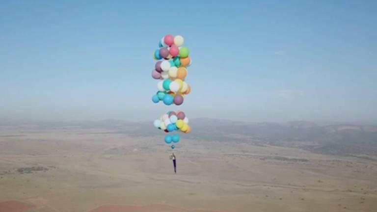 Um aventureiro britânico voou por 25 km suspenso por 100 balões de hélio na África do Sul.