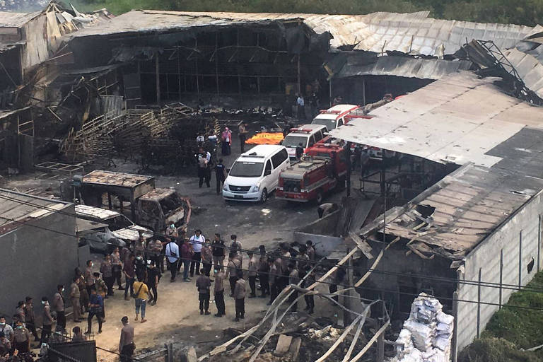 Police officers and rescuers inspect the site of an explosion at a firecracker factory in Tangerang, on the outskirts of Jakarta, Indonesia, Thursday, Oct. 26, 2017. The explosion and raging fire killed a number of people and injured dozens, police said. (AP Photo/Tatan Syuflana) ORG XMIT: JAK101