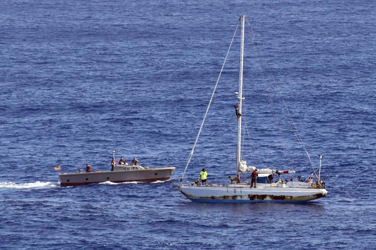O barco USS Ashland, da Marinha americana (esq.) se aproxima do barco onde estavam as duas mulheres
