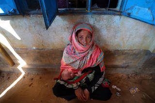 Ayesha Begum, 28, a Rohingya refugee woman holds her 1-month old son Noor, outside a registration centre in Kutupalong refugee camp near Cox's Bazar