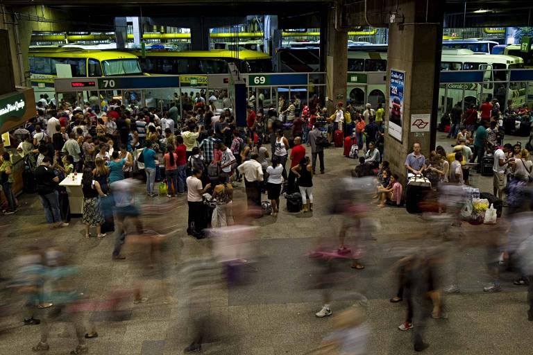 Portas de embarque no terminal rodoviário do Tietê. Pessoas esperam em filas em frentes às entradas dos ônibus, que estão parados na plataforma