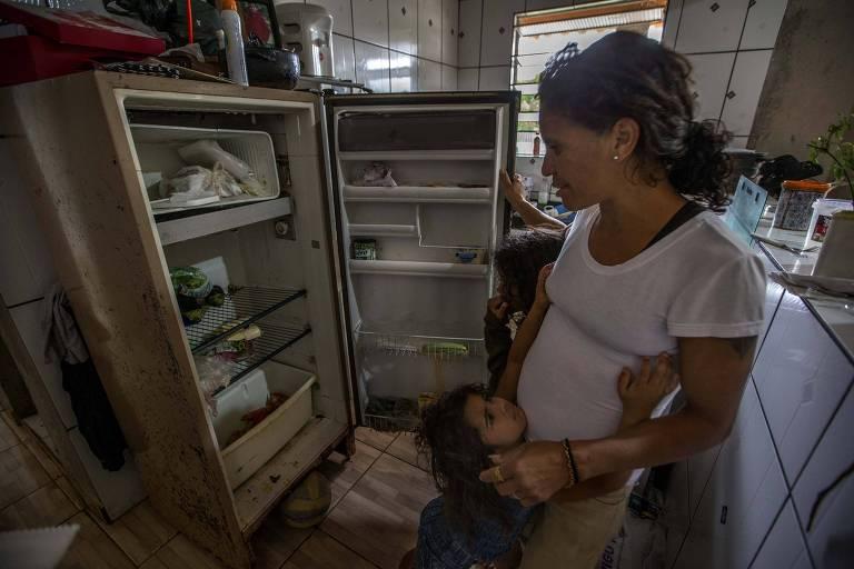 Valdeilma Alencar da Silva, 40, mostra a geladeira onde guarda legumes doados por feirantes; mãe de dez filhos, ela improvisa sopas quando a cesta básica acaba