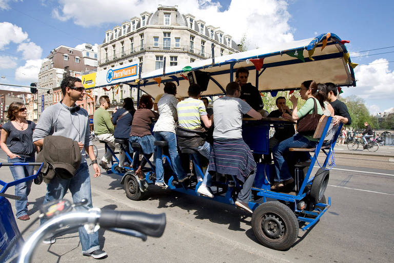 """Turistas pedalam enquanto bebem cerveja e cantam em um karaok� durante passeio em uma """"beer bike"""", em Amsterd�, na Holanda"""