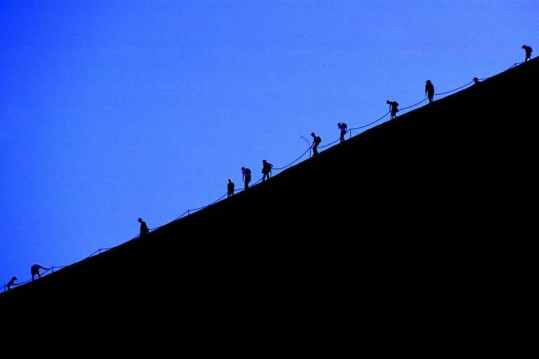 Turistas escalam o Uluru, na zona central da Austrália