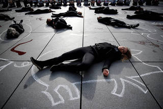 Supporters of People for the Ethical Treatment of Animals (PETA) lie in a heap on the pavement next to the Centre Pompidou modern art museum to raise awareness on World Vegan Day, in Paris