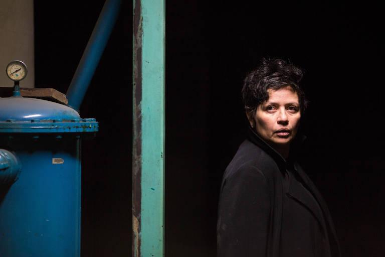 mulher branca de cabelos pretos curto olha, sem sorrir, para a câmera. ela está em um ambiente escuro, com um maquinário de metal azul