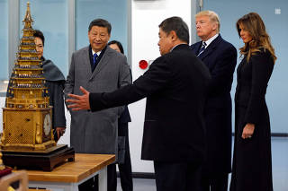 U.S. President Trump and Chinese President Xi look at an 18th Century Clock with a lifting tower as they tour the Conservation Scientific Laboratory of the Forbidden City in Beijing