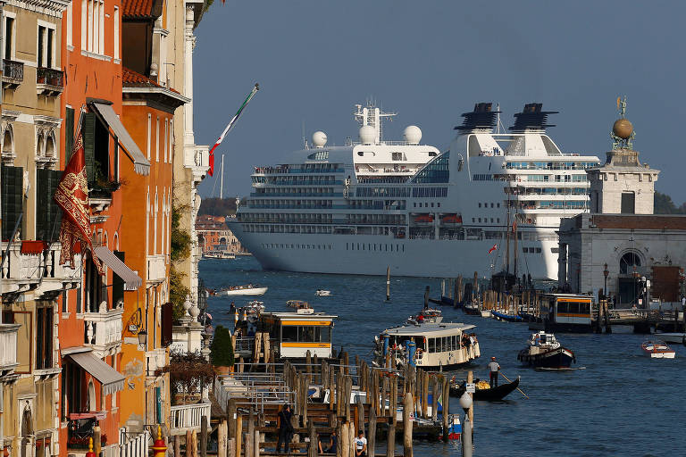 A imagem mostra o qu�o perto passam os cruzeiros que atracam em Veneza. � esquerda, est�o as laterais de pr�dios da cidade, com tons amarelados. Eles n�o aparentam ser muito altos, tendo no m�ximo cinco andares. A metade direita da foto � quase toda ocupada pelo mar, e no fundo, h� um grande cruzeiro de viagem.