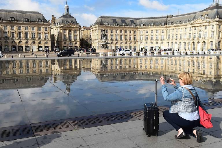 Turista em Bordeaux, na França. Visitar outras cidades além de Paris é outra dica para viajantes com orçamento apertado.