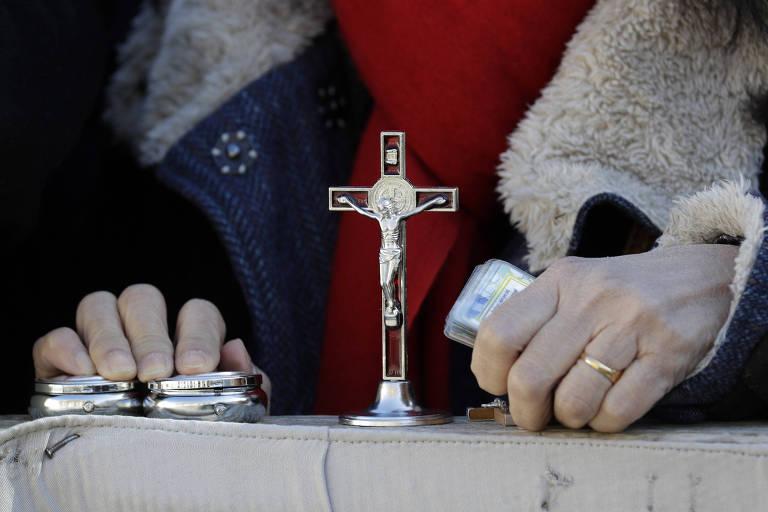 Mulher segura cruz e itens sacros durante audiência geral do papa Francisco nesta quarta (8)
