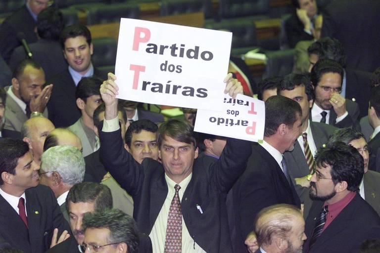 """Em 2003, o deputado federal Jair Bolsonaro segura um cartaz com a expressão """"Partido dos Traíras"""", em alusão ao PT, no plenário da Câmara dos Deputados"""