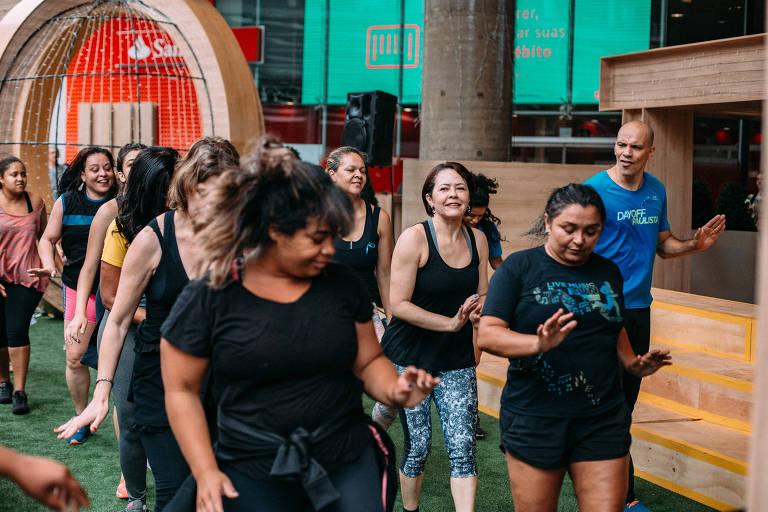 Pessoas dançam zumba na frente do Shopping Center 3