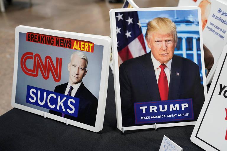 Cartaz que diz 'CNN é uma porcaria' aparece ao lado de foto de Trump em feira de armas na Pensilvânia