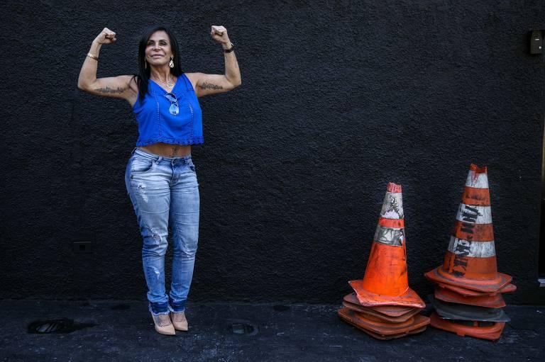 Gretchen veste calça jeans e blusa azul; ela dobra os braços com punhos para cima e faz força com os bíceps