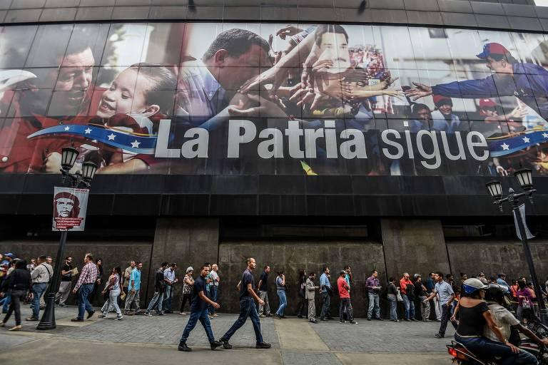 Pessoas fazem fila embaixo de painel com fotos de Ch�vez e Maduro e a frase 'A P�tria Continua