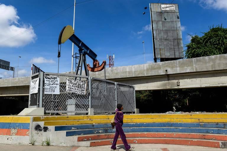 Pessoa passa por pra�a com est�tua em forma de bomba de petr�leo em Caracas