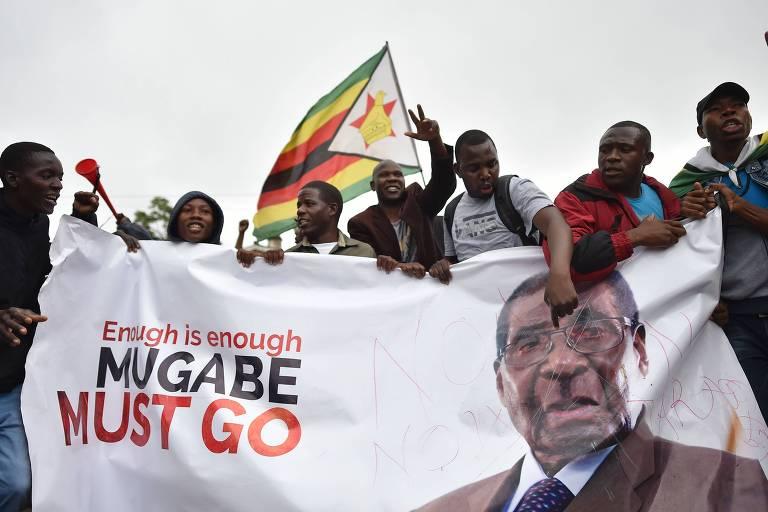 """Manifestantes seguram cartaz que diz """"Já é suficiente"""" e """"Mugabe tem de ir"""", em protesto em Harare (Zimbábue)"""