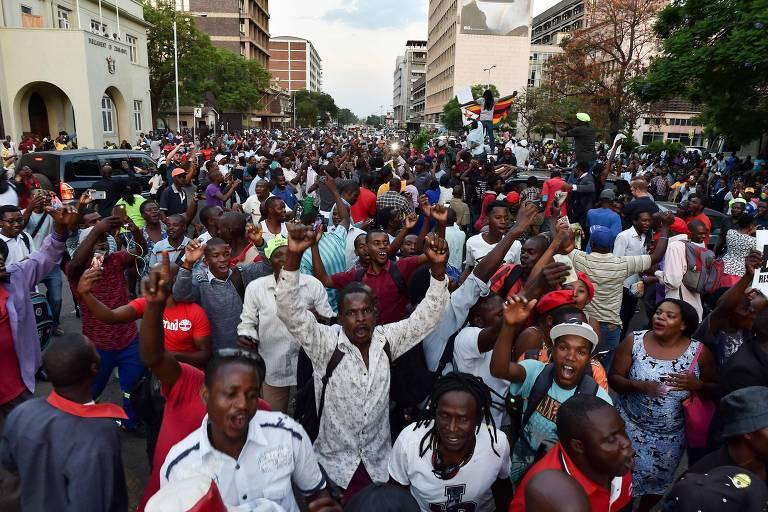 As pessoas celebram nas ruas de Harare, após a renúncia do presidente do Zimbábue, Robert Mugabe