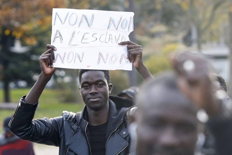 Manifestante protesta em Paris no sábado contra leilão de migrantes negros na Líbia