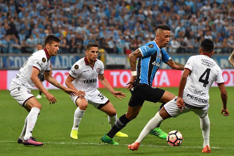 Lucas Barrios encara a marcação de três defensores do Lanús