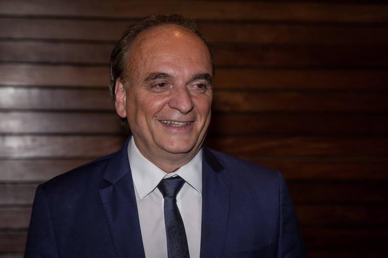 Paulo Dimas veste um terno azul e sorri para foto