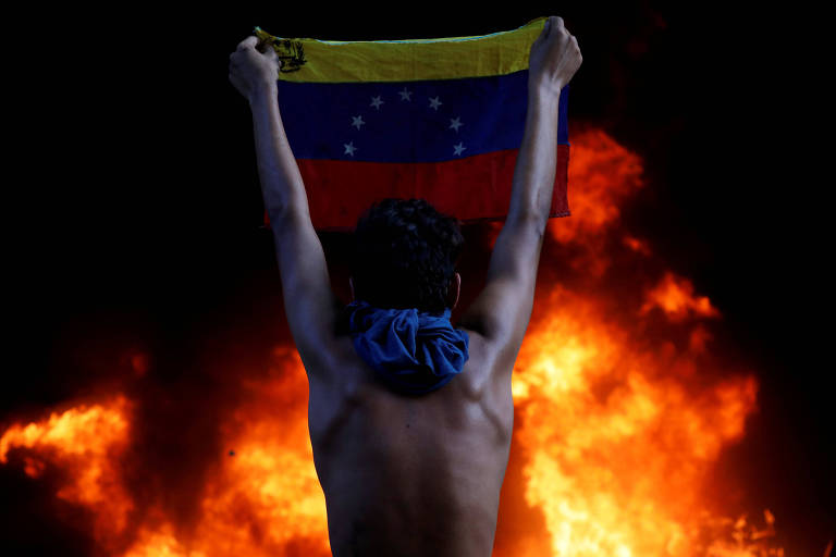 Manifestante segura bandeira venezuelana em protesto na sede do TSJ, em Caracas, em junho