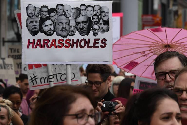 Mulheres carregam faixa com fotos de políticos e celebridades acusados de assédio sexual nos EUA