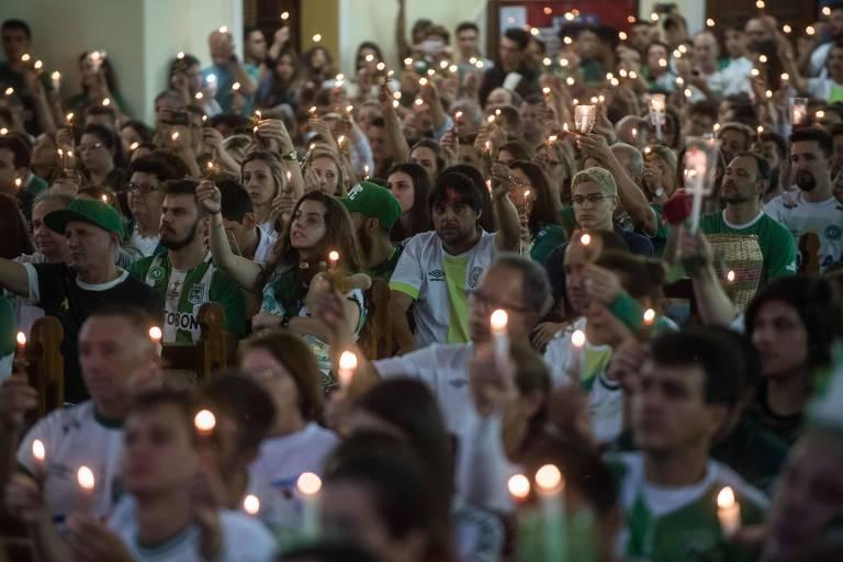 Pessoas acendem velas em cerimônia em homenagem às vítimas e sobreviventes do acidente com o avião da Chapecoense, um ano após a tragédia.