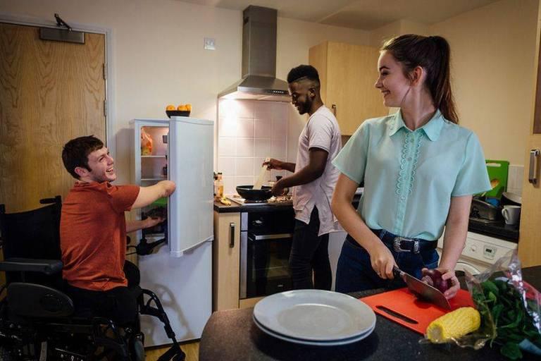 A foto mostra três pessoas em uma cozinha. Uma delas usa uma cadeira de rodas que abre uma geladeira adaptada, um pouco menor do que as usuais. Assim, ela tem fácil acesso às prateleiras. As outras pessoas estão de pé, viradas para as bancadas. Todos sorriem