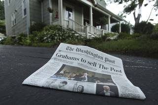 A morning edition of the Washington Post lies in a driveway after delivery in this photo illustration taken in Silver Spring, Maryland