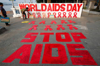A man places a placard as he prepares a message during an HIV/AIDS awareness campaign on the eve of World AIDS Day in Kolkata