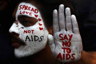 A student displays his face and hand painted with messages during an HIV/AIDS awareness campaign on the occasion of World AIDS Day in Chandigarh