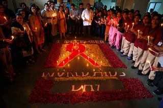 People hold candles as they pose around a ribbon during a ceremony to create awareness about HIV/AIDS on the eve of World AIDS Day in Ahmedabad