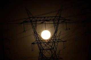 Pylons of high-tension electricity power lines are seen during sunrise in Brasilia