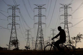 A man rides a bicycle near power lines connecting pylons of high-tension electricity, in Brasilia
