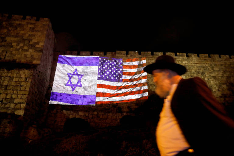 Homem passa em frente a projeção das bandeiras de Israel e EUA na Cidade Velha de Jerusalém