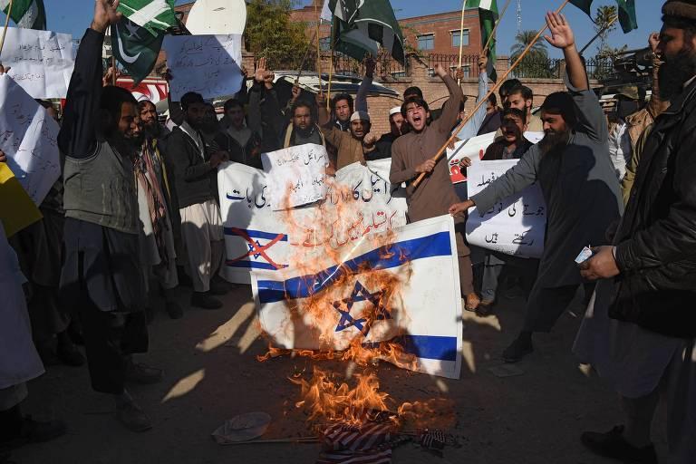 Manifestantes queimam bandeiras dos Estados Unidos e de Israel durante protesto em Peshawar, no Paquistão
