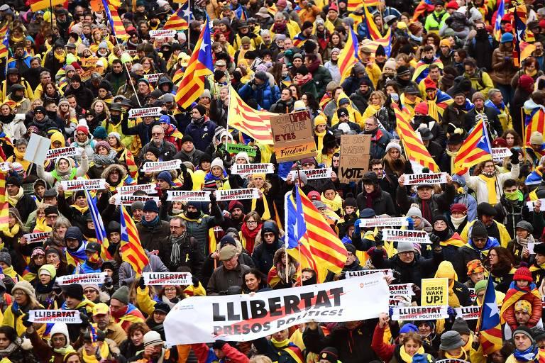 Pessoas acenam bandeiras catalãs de