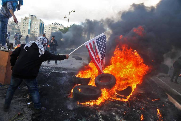 Manifestantes palestinos queimam bandeira dos EUA em protesto perto de Ramallah, na Cisjordânia