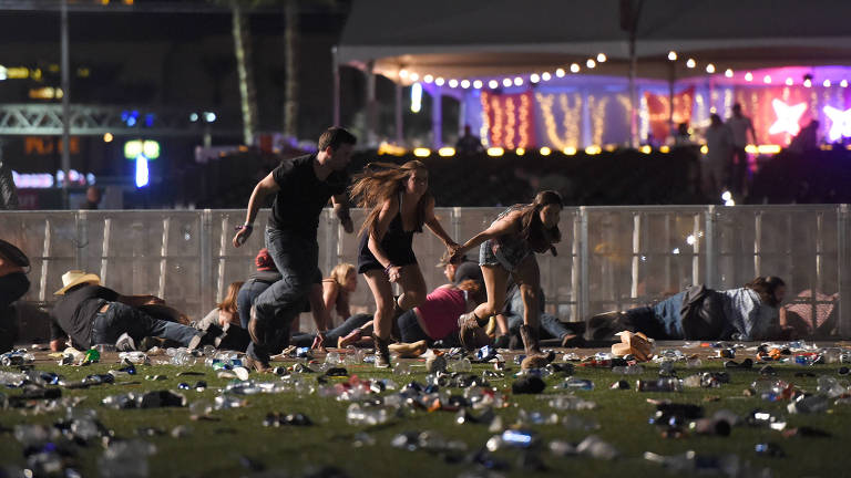 Pessoas correm de atirador que disparou de janela de hotel contra multidão em show em Las Vegas, em outubro, deixando 59 mortos e 527 feridos