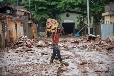 Homem carrega cadeiras de plástico em rua tomada por lamaçal em Rio Casca (MG) após enchente