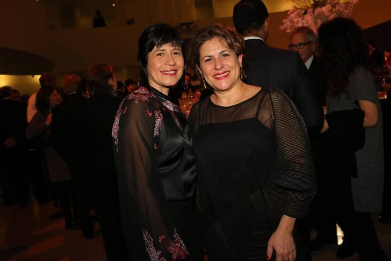Thelma Guedes e Duca Rachid, com vestidos preto, posam para foto