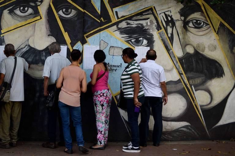 Eleitores checam locais de votação em Caracas, capital da Venezuela, no domingo