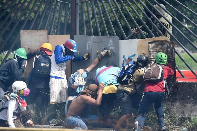 Grupo de manifestantes se protege de guardas nacionais durante protesto em Caracas em maio