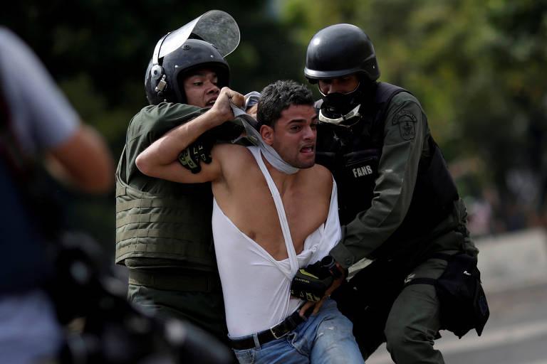 Membros da Guarda Nacional Bolivariana prendem manifestante em protesto em Caracas em julho
