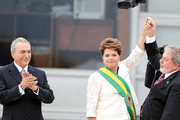 Dilma Rousseff entre o então vice-presidente, Michel Temer (à esq.) e Luiz Inacio Lula da Silva, no Palácio do Planalto, durante a posse para o primeiro mandato como Presidente da República