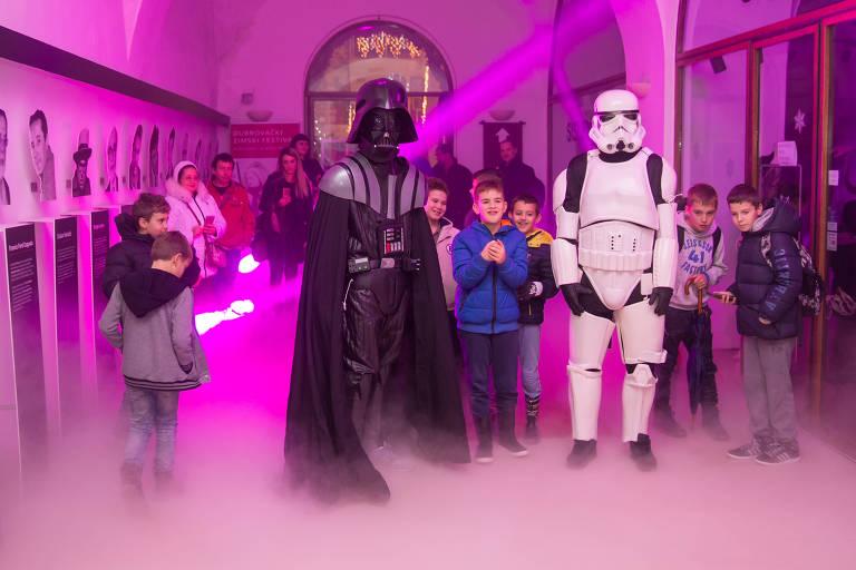 """Dois fãs de """"Star Wars"""" posam ao lado de crianças em um cinema de Dubrovnik, na Croácia, no dia 13, pré-estreia do último filme da saga"""