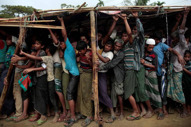 Rohingyas tentam se abrigar da chuva enquanto esperam por cobertores em campo em Bangladesh